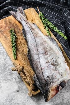 Carcasse de poisson d'aiglefin frais sur la planche à découper. fond gris.