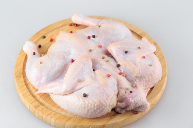 Carcasse de poulet cru sur la planche à découper isolée on white