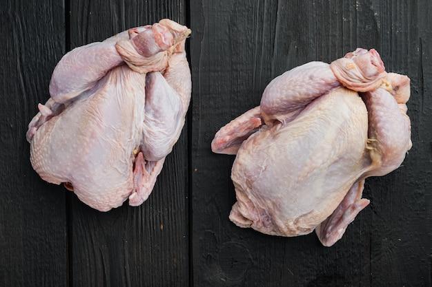 Carcasse de poulet entier cru frais, sur table en bois noir, vue de dessus