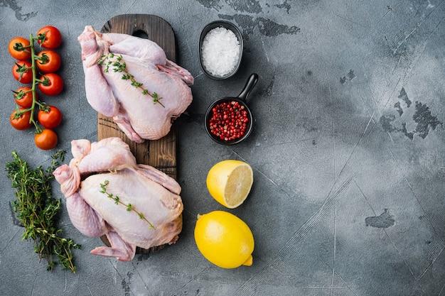 Carcasse de poulet entière crue fraîche avec des herbes et des ingrédients, sur fond gris
