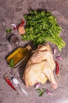 Carcasse de poulet entière crue pour un mode de vie sain. oiseau de ferme en plein air avec des feuilles de persil, des gousses d'ail, des épices et de l'huile de cuisson. une lumière dure à la mode, une ombre sombre, un fond en pierre, une vue de dessus