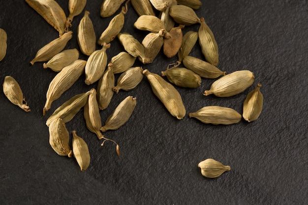Cardamome épice macro détail sur pierre d'ardoise noire