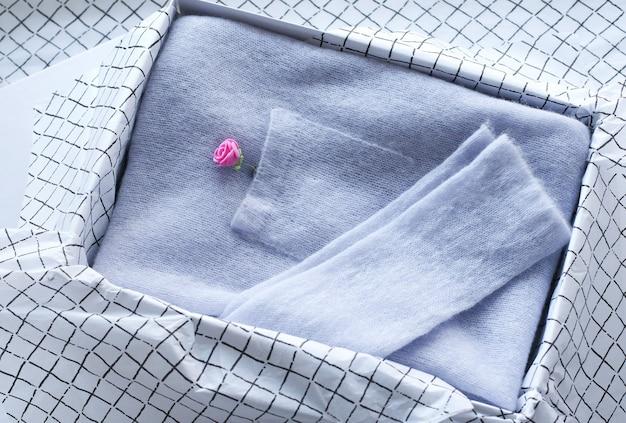 Cardigan tricoté de couleur pastel sur une boîte