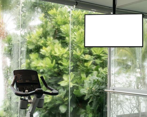 Cardio training: tapis roulant avec maquette d'écran blanc, grandes fenêtres avec vue sur l'océan pleuvant à l'extérieur.