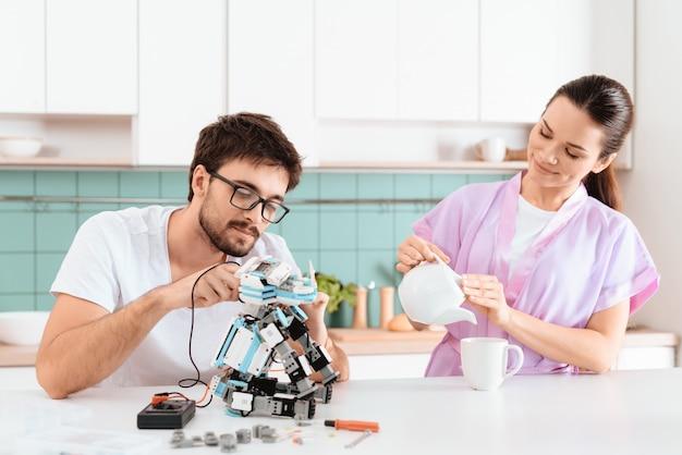 Care girl apportez du thé à un homme qui travaille avec un robot.