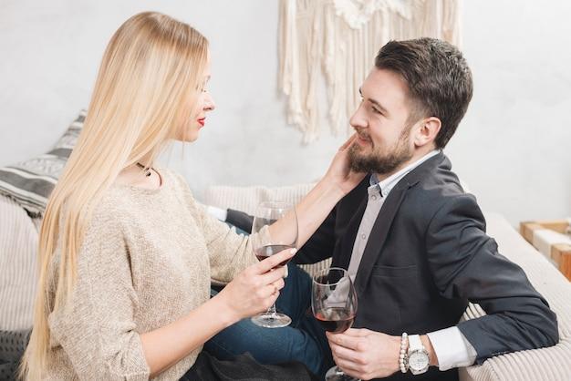 Caressant jeune couple avec du vin