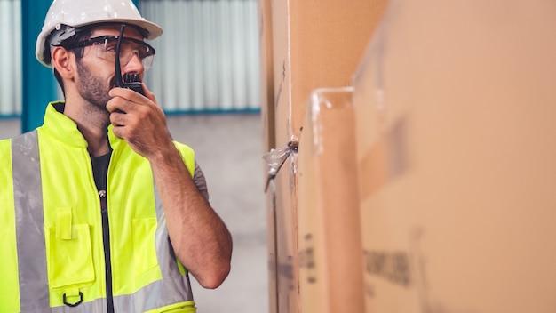Un cargo professionnel parle sur une radio portable pour contacter un autre travailleur