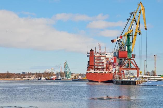 Cargos amarrés et grues portuaires au port. port maritime, parc à conteneurs, terminal de porte-conteneurs, chantier naval. affaires et commerce, logistique. scène industrielle d'hiver.