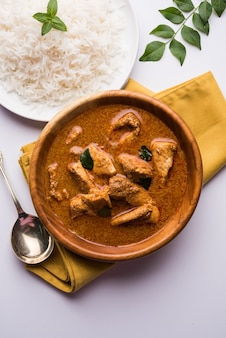 Cari de poisson savoureux servi avec du riz basmati cuit blanc avec des feuilles de curry en arrière-plan, nourriture indienne côtière préférée