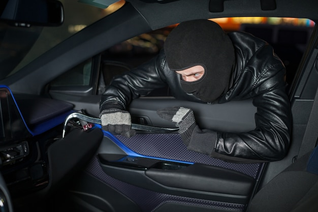 Carjacker déverrouille la boîte à gants avec pied de biche. homme voleur avec cagoule sur sa tête de voiture de piratage. concept de danger de détournement de voiture. crime de transport automobile
