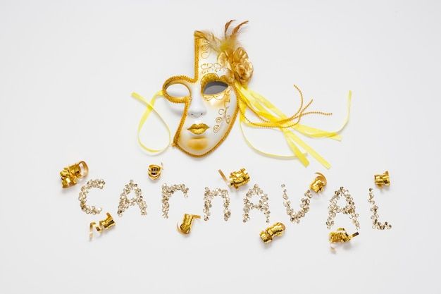 Carnaval écrit en paillettes et masque doré