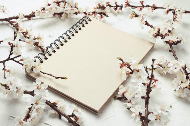 Carnet et un brin de fleurs de cerisier en pierre