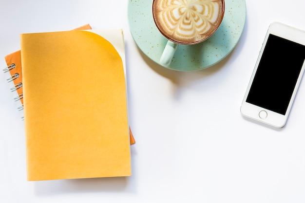Carnet brun et café avec smartphone sur fond isolé.