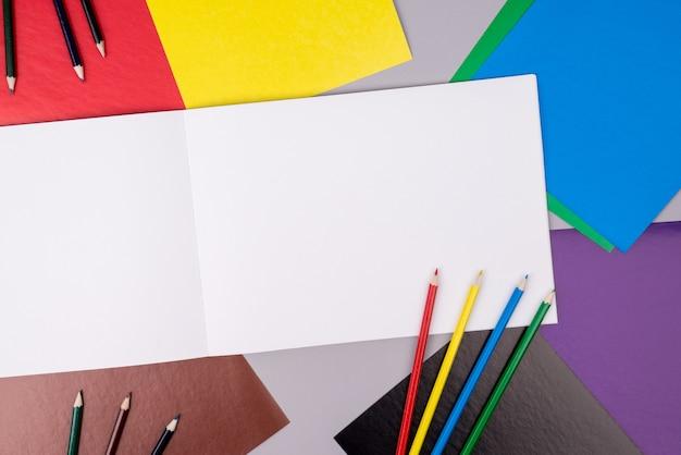 Carnet de croquis avec des crayons de couleur et du papier de couleur sur gris