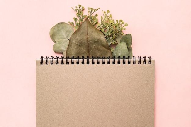 Carnet de croquis mocap bloc-notes sur fond rose avec branche d'eucalyptus et feuille de ficus