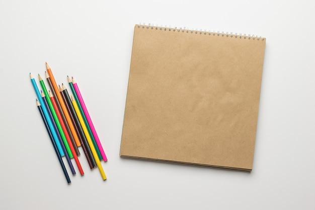 Un carnet de croquis ouvert et un ensemble de crayons de couleur sur fond blanc. accessoires pour la créativité.