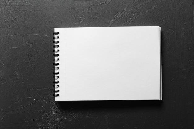 Carnet de croquis vierge avec des pages blanches isolées sur fond noir