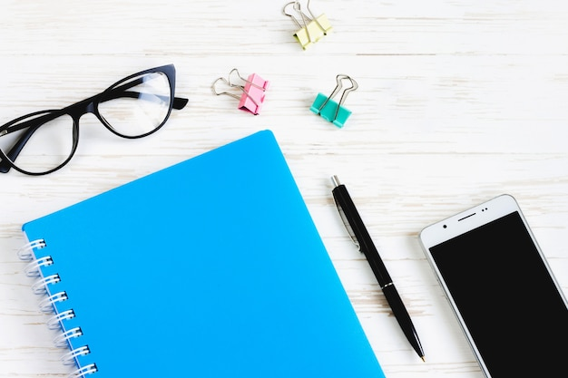Carnet fermé, stylo, lunettes, téléphone mobile, une tasse de café sur une table en bois blanche, plat poser, vue de dessus. bureau table bureau