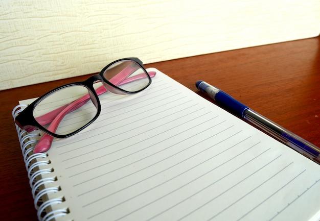 Carnet de journal avec un stylo et des lunettes sur la table en bois.