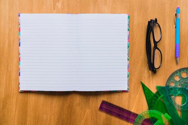 Carnet, lunettes, plis et stylo