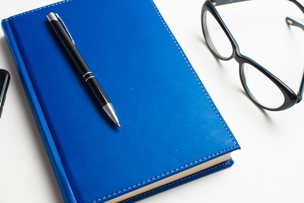 Carnet avec des lunettes et un stylo, livre avec des lunettes, carnet bleu avec des lunettes, livre avec une tasse de thé