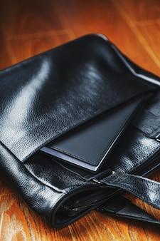 Carnet noir furtivement hors de la poche d'un gros plan de sac en cuir noir, macro matériaux naturels faits à la main.