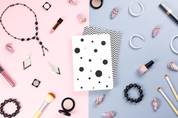 Carnet de notes et accessoires de beauté femme à plat sur table pastel