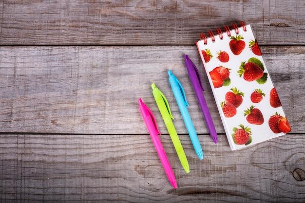Carnet de notes aux fraises et ensemble de stylos de couleurs sur fond en bois