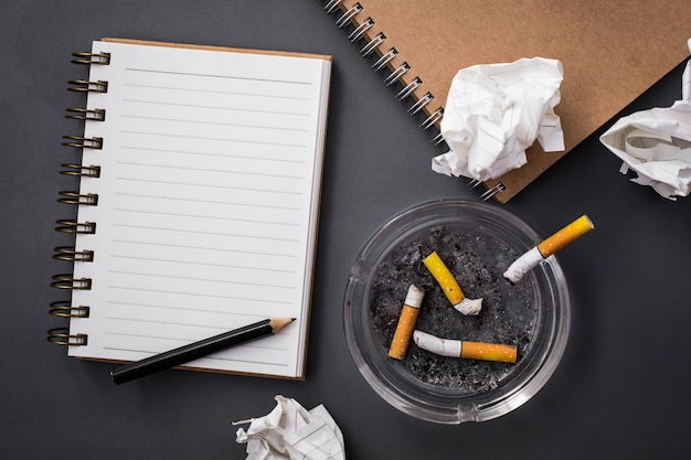Carnet de notes avec des cigarettes et un cendrier