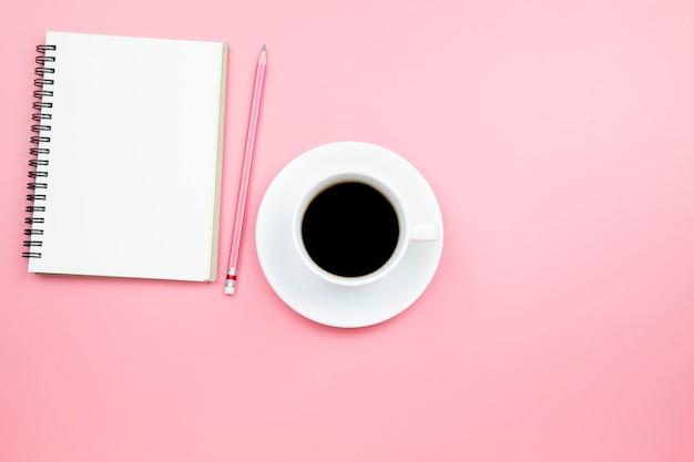 Carnet de notes crayon café noir sur fond rose style pastel