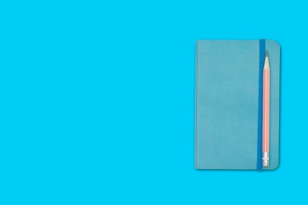 Carnet de notes et crayon isolé sur bleu