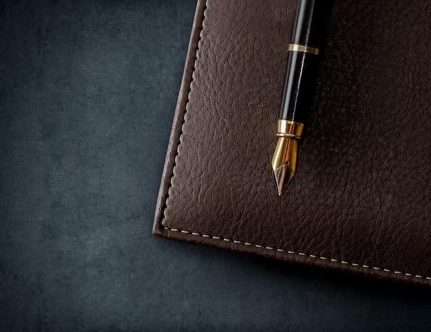 Carnet de notes en cuir marron avec stylo plume. fond d'affaires.