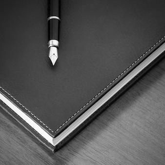 Carnet de notes en cuir noir et stylo plume sur le bureau