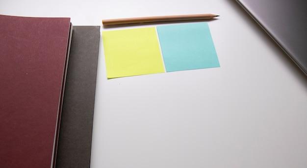 Carnet de notes et fournitures de bureau près de l'ordinateur portable sur la table blanche