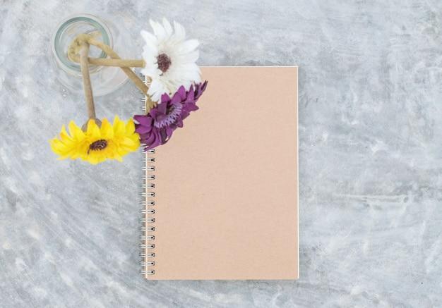 Carnet de notes gros plan avec une fleur artificielle colorée sur fond de table en béton