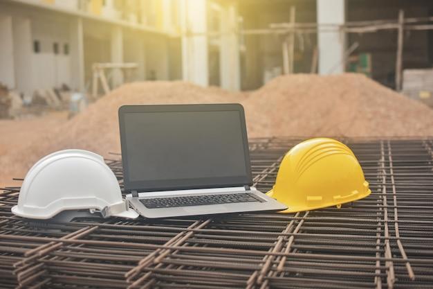 Carnet de notes d'ordinateur casque jaune et casque de pentecôte sur la construction de bâtiments en acier