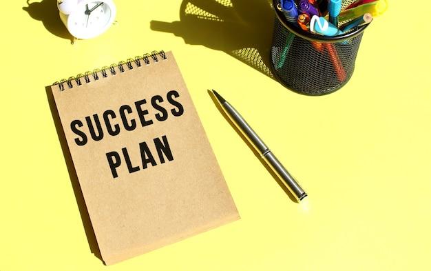 Carnet de notes en papier artisanal avec texte plan de succès avec papeterie. couleur de fond jaune.