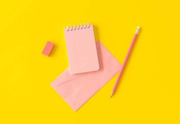 Carnet de notes pastel avec crayon et enveloppe