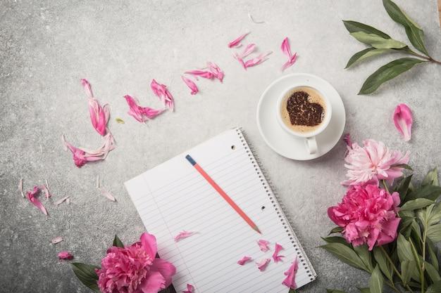 Carnet de notes, pivoines et tasse de café sur fond de béton clair avec texte juin