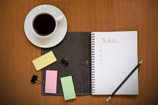 Carnet de notes recyclé avec une liste de tâches en main dans la note papier