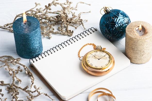 Carnet de notes vierge, bougies d'arôme d'or bleu et jouets de noël sur rustique en bois