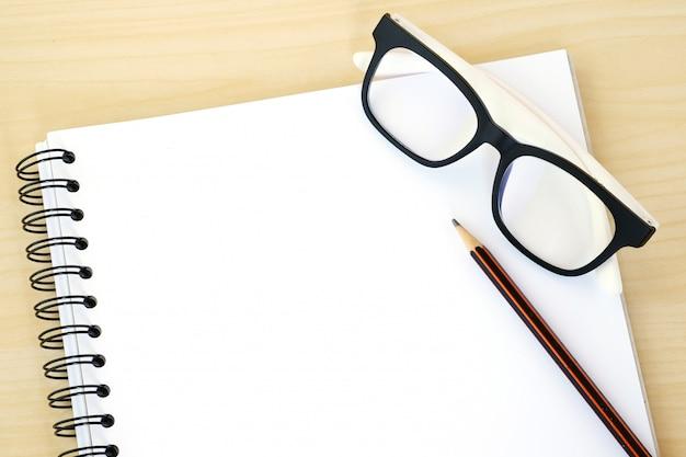 Carnet de notes vierges, lunettes et crayon sur fond de bois, modèle