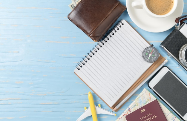 Carnet de notes vierges avec passeport téléphone intelligent et appareil photo vintage sur fond de bois ancien, se préparer à tra