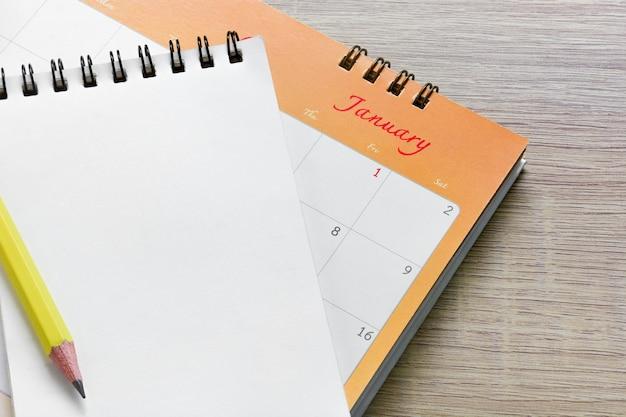 Carnet ouvert vide avec un crayon de couleur jaune placé sur le calendrier de janvier