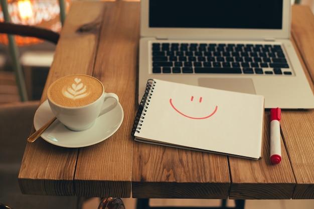 Carnet avec un visage souriant dessiné placé sur la table en bois entre un ordinateur portable et une tasse de café