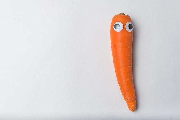 Carotte avec drôle de visage et yeux écarquillés sur le mur blanc. concept de végétarisme