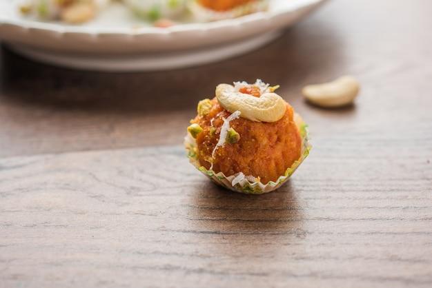 Carotte halwa laddu ou boules sucrées, servies dans une assiette avec des garnitures de fruits secs. mise au point sélective