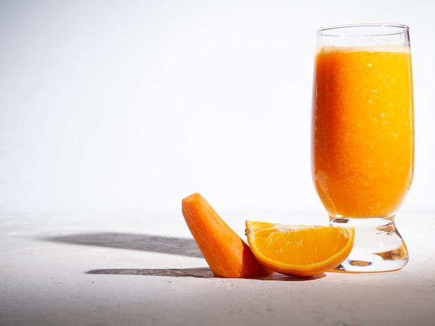 Carotte orange fraîche dans une tasse en verre sur fond blanc avec ombre. copyspace.