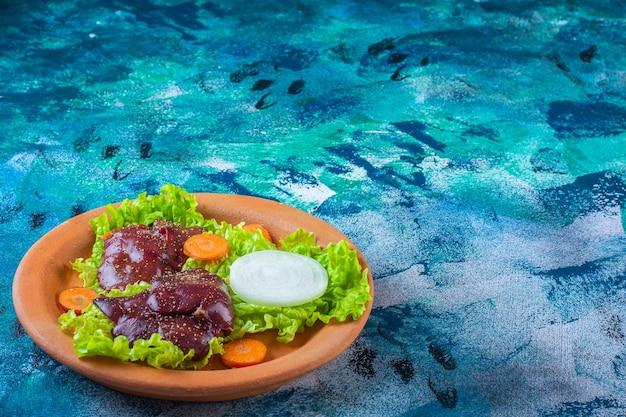 Carotte tranchée, feuilles de laitue oignon et foie de poulet sur un bol en argile