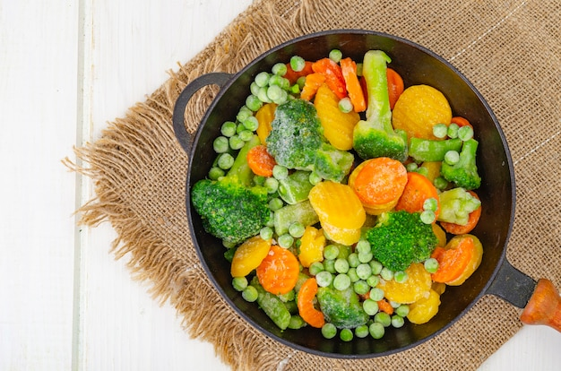 Carottes, brocoli et pois verts surgelés dans une poêle